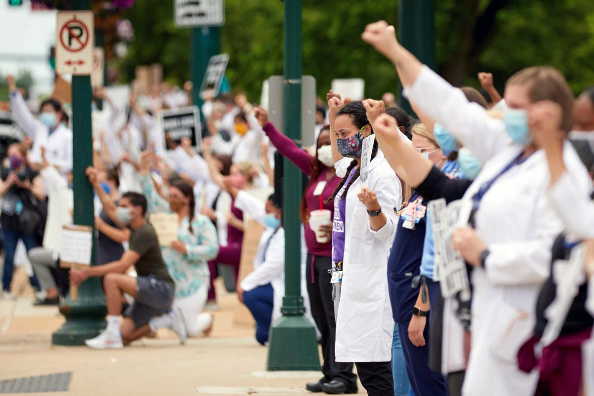 Hundreds of people, some wearing scrubs and white coats, stand on a sidwalk with signs and raised fists.